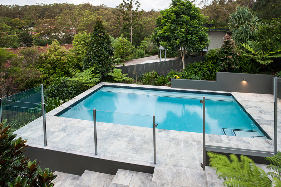 Modern swimming pool with a glass fence on the tile floor covered with a garden  with green trees, there is a jungle from a distance with some house through it