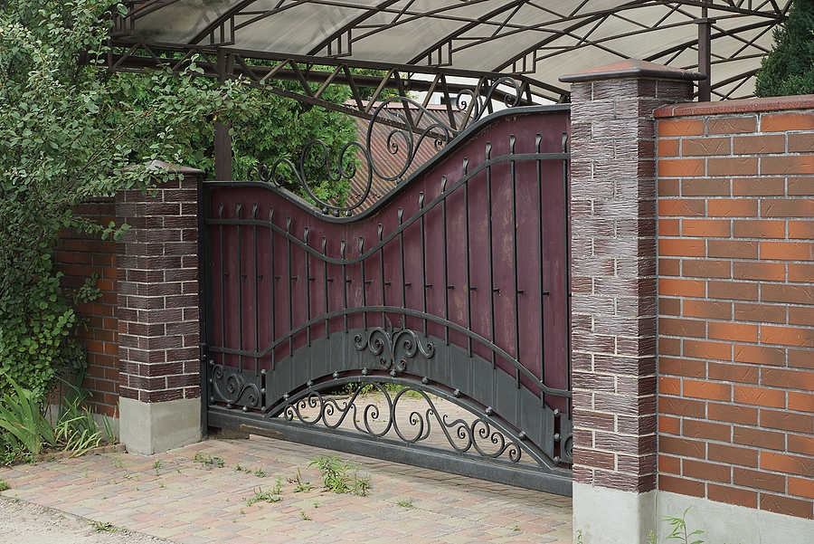 one metal gate with a black iron pattern and part of a wall of a fence made of brown bricks on the street